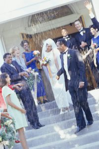 Guests throwing rice at bride and groom in front of church