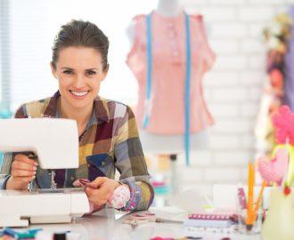 Happy seamstress sewing in studio